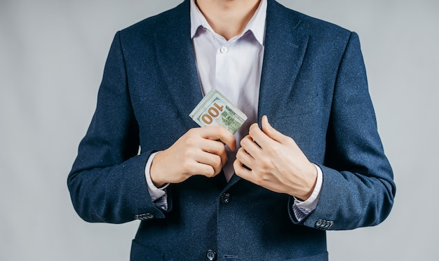 Businessman in a black suit putting money in his pocket