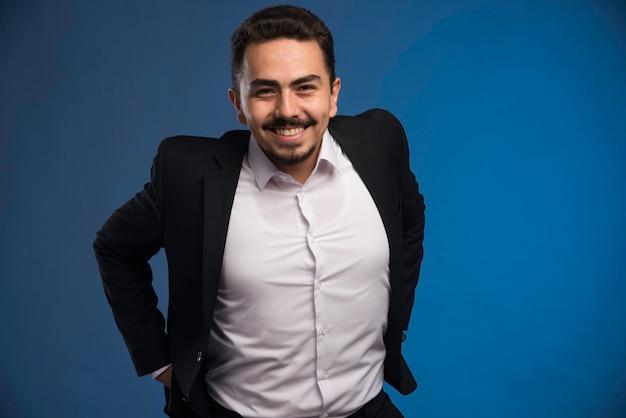 Uomo d'affari in vestito nero che sorride positivamente.