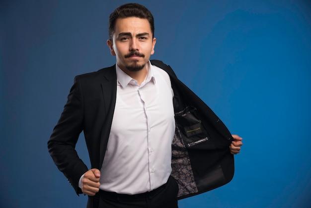 Uomo d'affari in abito nero, tirando fuori la giacca.
