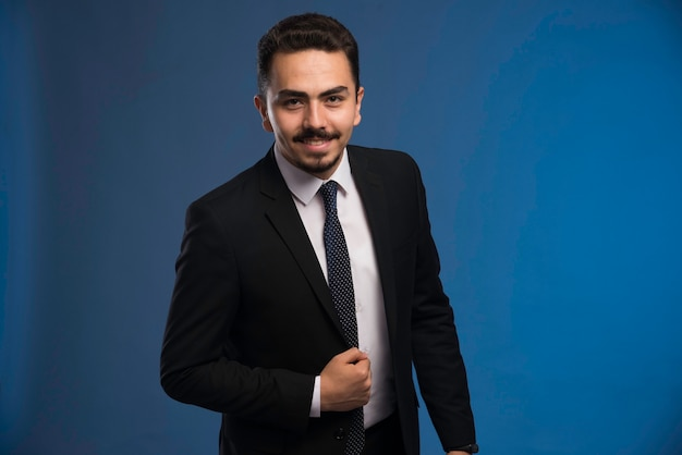 Uomo d'affari in abito nero con una cravatta in posa positiva.
