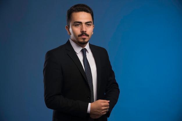 Uomo d'affari in abito nero con una cravatta in posa.