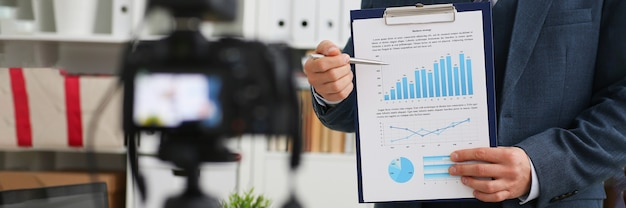 사업가 블로거는 상업 지표가 있는 카메라 비즈니스 차트를 보여줍니다. 온라인 비즈니스 개발 과정