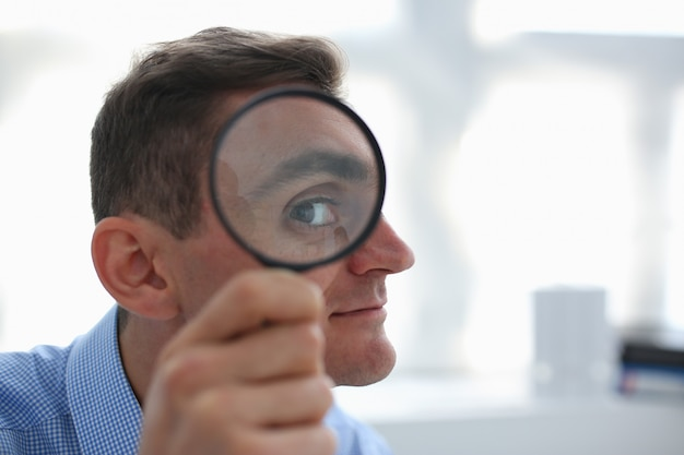 A businessman in blue shirt is holding a magnifying