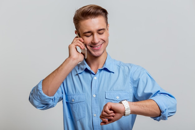 Businessman in blue shirt smiling, talking on the phone.