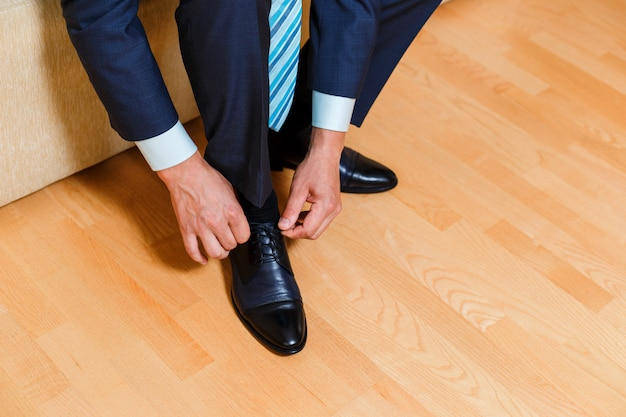 Businessman in blue suit and tie tying his shoelaces