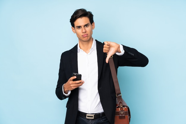 Businessman over blue wall showing thumb down sign