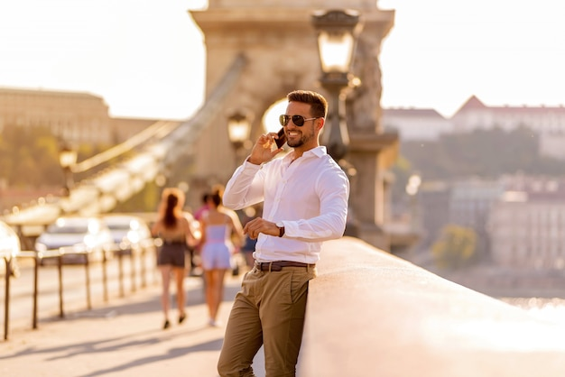 A businessman on a bridge and talking on his phone