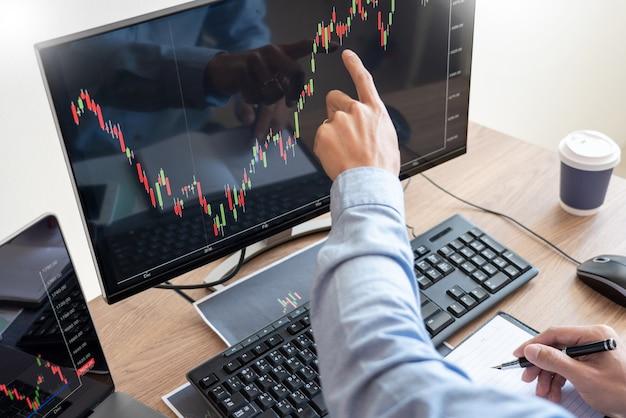 Бизнесмен-брокер анализирует графики финансовых данных и отчеты на экране