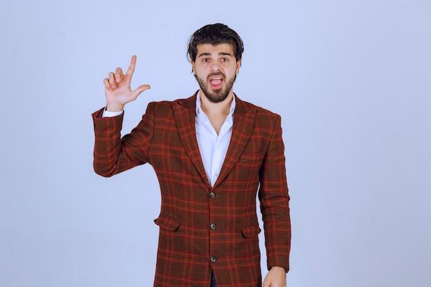 Uomo d'affari in giacca marrone che fa il segno della mano del perdente.