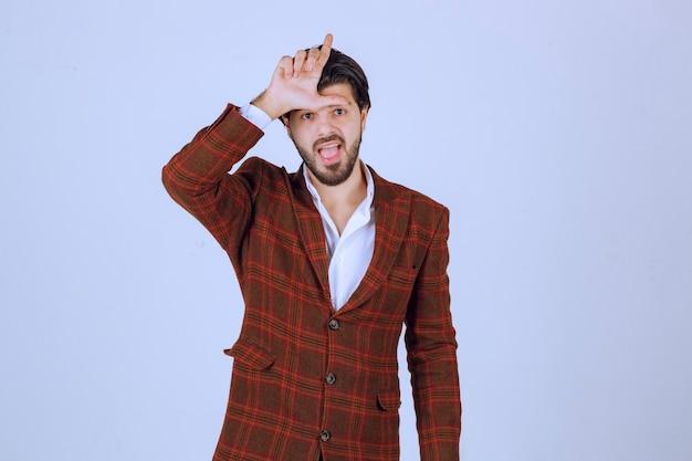 Businessman in brown jacket making loser hand sign.