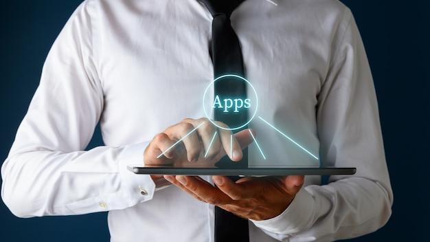 手袋をはめたアプリのサインで彼のデジタルタブレットを閲覧しているビジネスマン