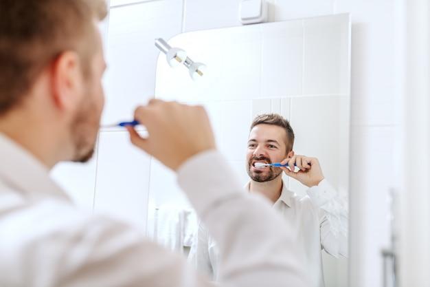 Бизнесмен, чистящий зубы, стоя перед зеркалом в ванной комнате.