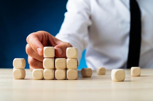 事業投資の概念的なイメージで木製のダイスの構造を構築し、立ち上がるビジネスマン。