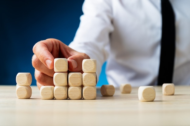 Businessman building a structure of wooden dices in a conceptual image of business investment and start up.