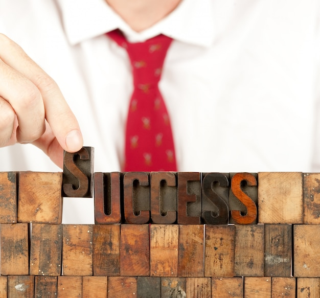 Businessman building success word in letterpress on white wall