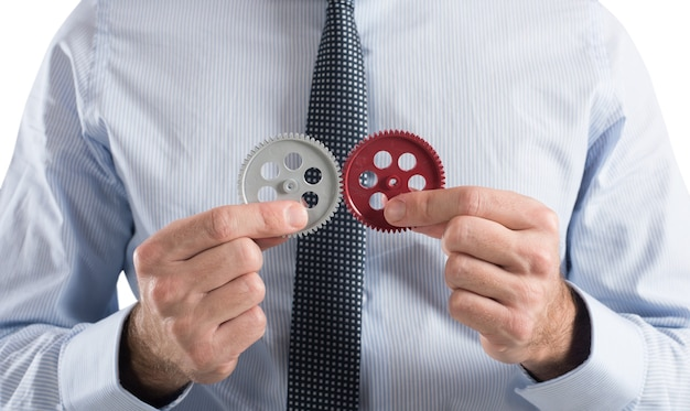 Бизнесмен строит бизнес-систему как шестеренчатый механизм