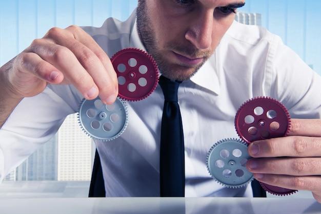 Businessman builds a business system as a gears mechanism