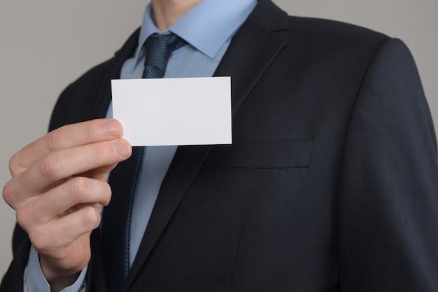 ビジネスマン、名刺を示すビジネスマンの手持ち-灰色の背景にクローズアップショット