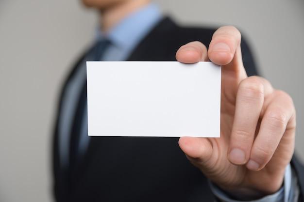 ビジネスマン、名刺を示すビジネスマンの手持ち-灰色のテーブルのクローズアップショット。白紙を見せてください。紙の名刺。