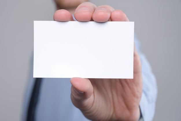 ビジネスマン、名刺を示すビジネスマンの手持ち-灰色の壁にショットをクローズアップ。白紙を見せてください。紙の名刺。