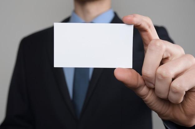 ビジネスマン、名刺を示すビジネスマンの手持ち-灰色の壁にショットをクローズアップ。白紙を見せてください。紙の訪問カード。