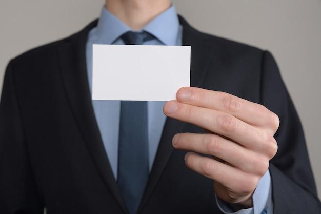 ビジネスマン、ビジネスマンの手持ちの名刺のクローズアップショットを灰色で表示