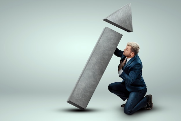 A businessman in a business suit holds, turns the direction arrow