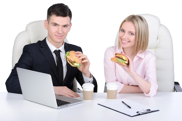 Businessman and business woman eating in the office.