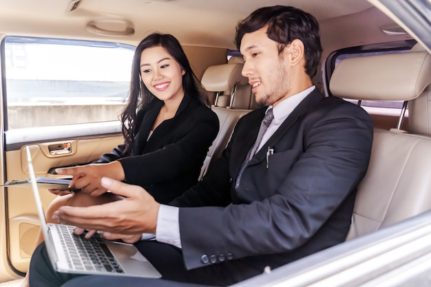 Businessman and business woman sitting in car, working on laptop, work anytime and anywher