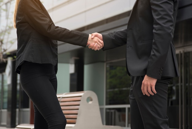 Businessman and businesswoman are shaking hands in front of the office building