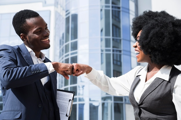 Businessman and businesswoman bumping their fist in front of corporate building
