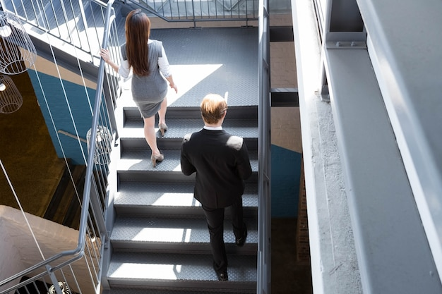 Businessman and businesswoman climbing staircase in office