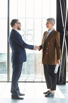 Businessman and businesswoman greeting each other at office they shaking hands