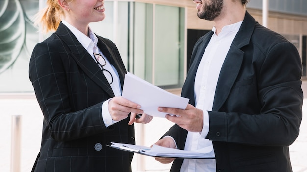 Businessman and businesswoman holding documents in hands