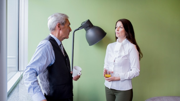 Businessman and businesswoman interacting during a break in the office