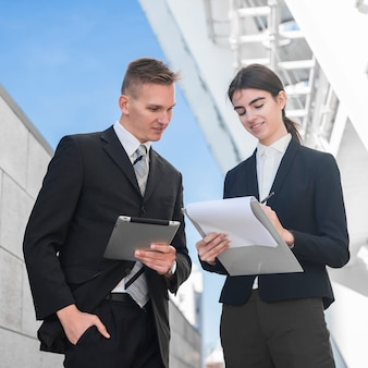 Businessman and businesswoman looking at clipboard