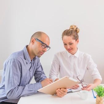 Uomo d'affari e donna di affari che esaminano ridurre in pani digitale