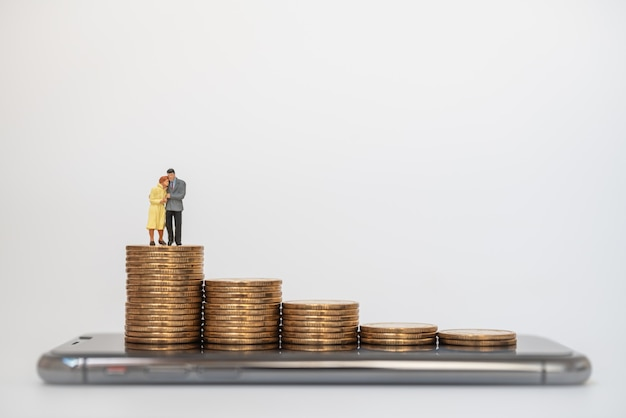 Businessman and businesswoman miniature figure people hug and walking on stack of gold coins