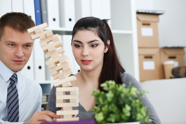 Businessman and businesswoman plays in strategy hand rearranging wooden blocks involved during break at work in office sitting table gaming pile fun joy pastime concept.