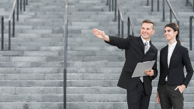 Businessman and businesswoman pointing somewhere
