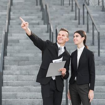 Businessman and businesswoman pointing upwards