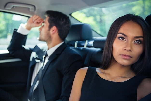 Businessman and businesswoman riding on back seat in car