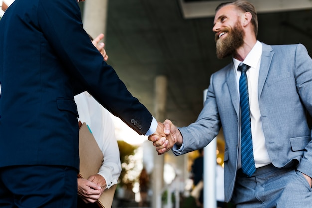 A businessman and a businesswoman shaking hands in agreement