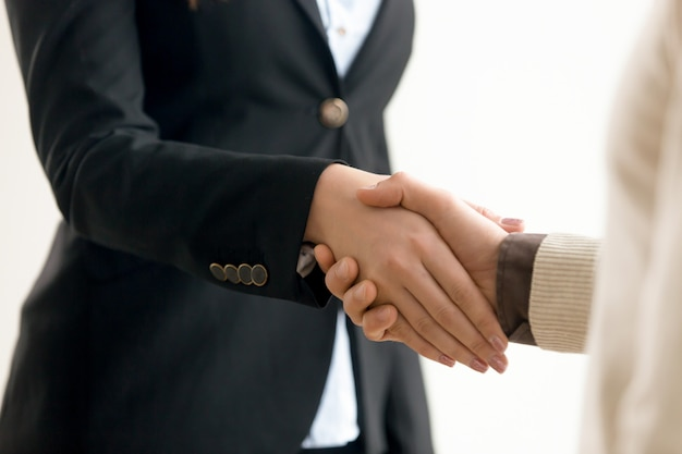 Businessman and businesswoman shaking hands, business handshake close up view