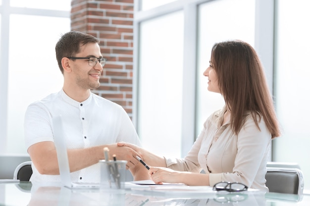 Businessman and businesswoman shaking hands while sitting at the desk. concept of cooperation