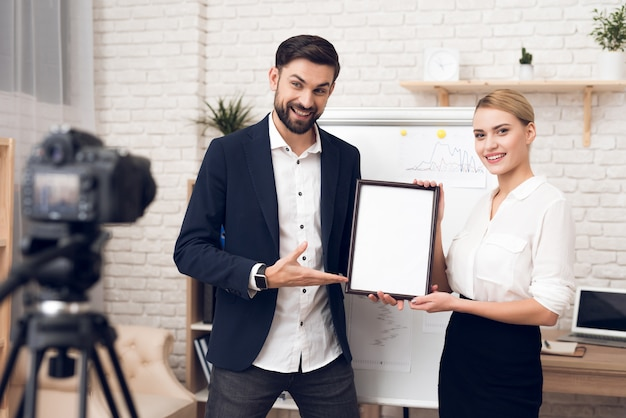 Businessman and businesswoman showing blank diploma.