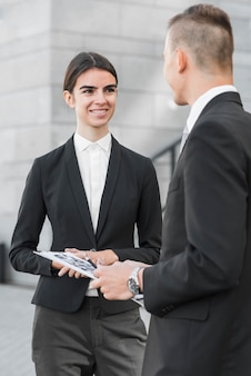 Businessman and businesswoman talking to each other