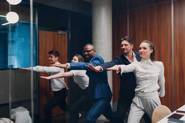 Businessman and businesswoman team doing warm up and yoga exercises before office meeting business h...