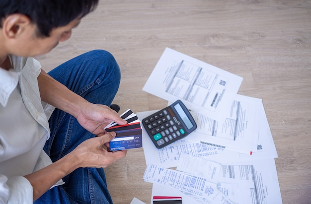 Businessman or butler is sitting at the press of various expense calculators on invoices and credit card debt. men are stressed with the debt to pay monthly. debt concept