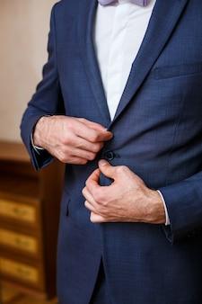 Businessman buttons up on blue jacket